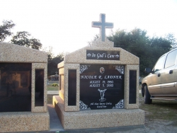 Single deluxe mausoleum with granite inlays in the columns and a cross on a foundation/slab in Pass Christian, MS