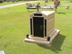 Over-and-under (stack) deluxe mausoleum with granite in the columns, a cross, two vases and step-up trim pieces in Millbrook, AL