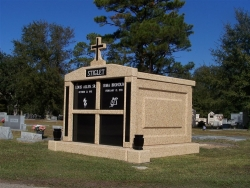 Four-space deluxe mausoleum with cross, granite inlays in the columns, vases on pedestals in Pascagoula, MS