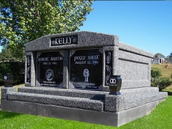 Side-by-side deluxe mausoleum deep gray with engraved inlays in the columns, vases on pedestals, step-up trim pieces on a foundation/slab in Taylorsville, MS