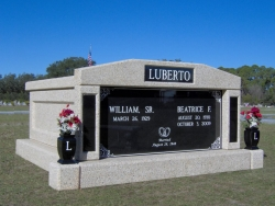 Side-by-side deluxe mausoleum with granite inlays in the columns and vases on pedestals in Eastpoint, FL