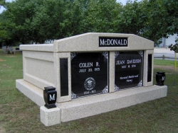 Side-by-side deluxe mausoleum with granite inlays in the columns and vases on pedestals in Bonaire, GA