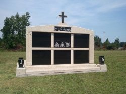 Six-space wide mausoleum with cross, fluted columns, vases on pedestals, step-up trim pieces on a foundation in Raiford, FL