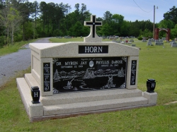 Side-by-side deluxe mausoleum with a cross, engraved granite inlays in the columns, vases on pedestals, step-up trim pieces on a foundation/slab in Mize, MS