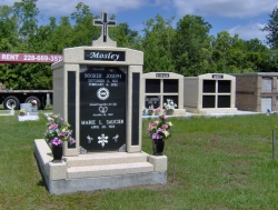 Over-and-under (stack) deluxe mausoleum with granite in the columns, a cross, two vases on pedestals, step-up trim pieces on a foundation/slab in Bay St. Louis, MS