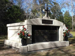 Side-by-side deluxe mausoleum with fluted columns and a cross, vases on pedestals, on a foundation/slab in Thomasville, AL