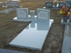 Double upright headstone with a vase and granite ledger in Pascagoula, MS