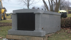 Granite single mausoleum with Roman columns on a foundation/slab in Landover, MD