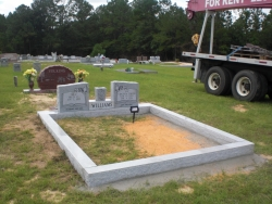 Double upright headstone with a vase and granite coping in Biloxi, MS