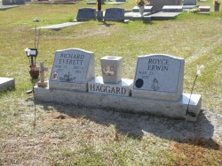 Double gray granite slant monument on a base with a vase and photo plaques in Lucedale, MS
