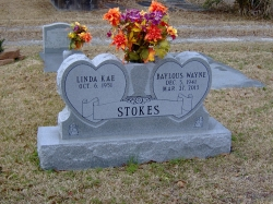 Double upright headstone with two hearts and a vase on a base