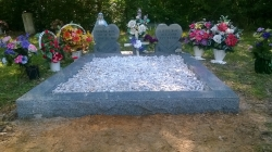 Two heart shape upright headstones with a vase and granite coping
