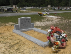 Single granite upright headstone with 2 vases and matching granite coping in Vancleave, MS