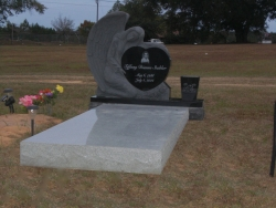 Single upright headstone with a large angel with heart and vase and granite ledger in Bayou LaBatre, AL