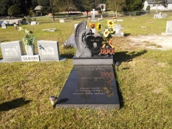 Single upright headstone with a large angel with a heart, vase, turned vase on a base with a black ledger in Saucier, MS