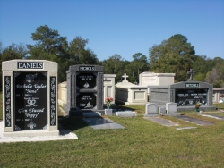 Deluxe over-and-under (stack) white mausoleum with engraved granite inlays in the columns, a deluxe over-and-under deep gray mausoleum with fluted columns, and a deluxe side-by-side deep gray mausoleum with fluted columns in Pascagoula, MS