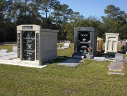 Deluxe over-and-under (stack) white mausoleum with engraved granite inlays in the columns, a deluxe over-and-under deep gray mausoleum with fluted columns in Pascagoula, MS