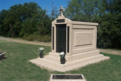 Over-and-under (stack) deluxe mausoleum with granite in the columns, a cross, two vases and step-up trim pieces on a foundation/slab with two benches in Henrietta, TX