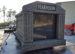 Single deluxe mausoleum in deep gray with a tapered base and fluted columns on the trailer strapped down and ready to be delivered to Williston, FL