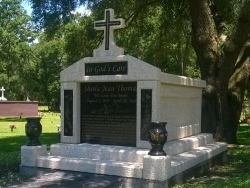 Single deluxe mausoleum engraved granite inlays in the columns and a cross and vases on pedestals with step-up trim pieces on a foundation/slab in Atlantic Beach, FL