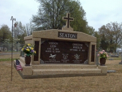 Side-by-side deluxe mausoleum with cross, granite inlays in the columns, vases and pedestals, step-up trim pieces on a foundation/slab in Dyersburg, TN