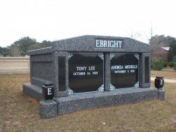Side-by-side deluxe mausoleum in deep gray with granite inlays in the columns, split doors, vases on pedestals in Mobile, AL