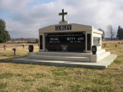 Side-by-side deluxe mausoleum with cross and granite in the columns, vases on pedestals, engraved wide panels and step-up trim pieces on a foundation/slab in Clarksdale, MS