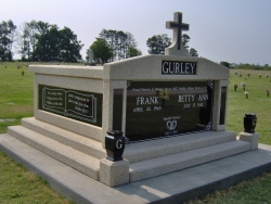 Side-by-side deluxe mausoleum with cross and granite in the columns, vases on pedestals, engraved side panels and step-up trim pieces on a foundation/slab in Clarksdale, MS